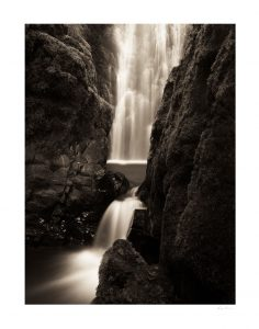 waterfall with blurred water amidst rocks